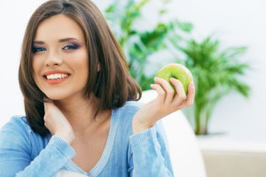 Toothy smiling young woman hold green apple.